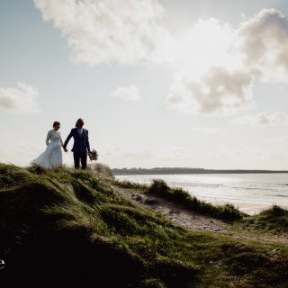 Bride and groom in the sand dunes at spanish point